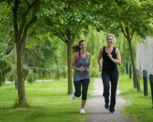 Two ladies running through Ragdale Hall grounds