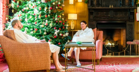 Guests relaxing by tree and open fire on Christmas spa break