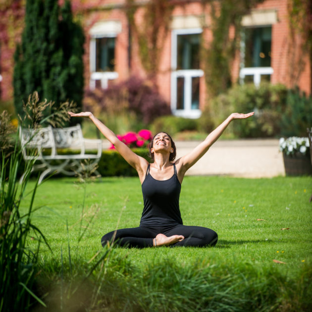 Lady practicing Yoga out side the front of Ragdale Hall