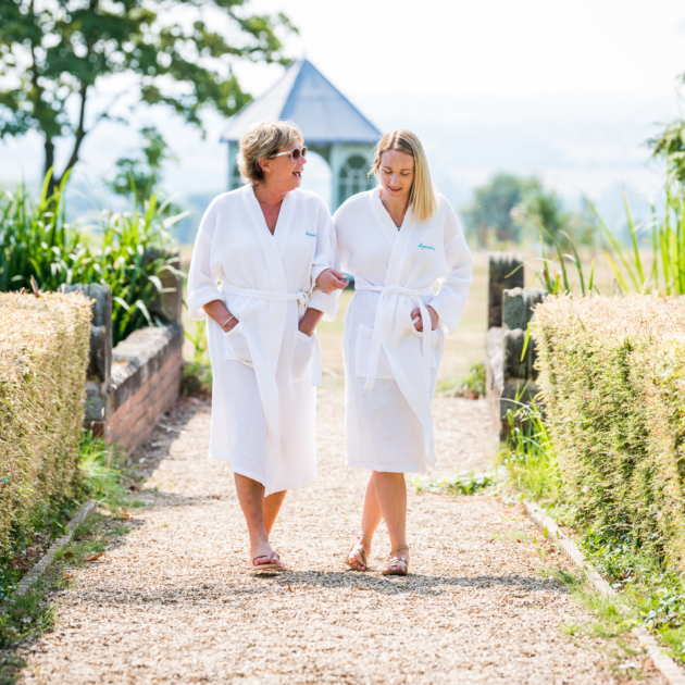 two ladies in robes walking in gardens
