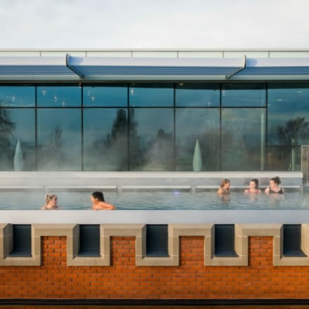 Guests in roof top pool during the day during spa break