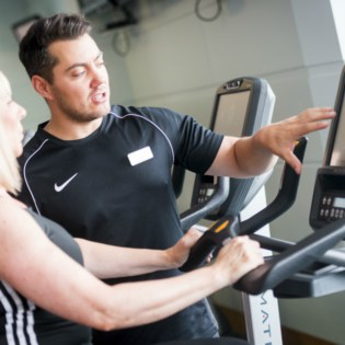 Fitness instructor explaining the exercise machine to a guest
