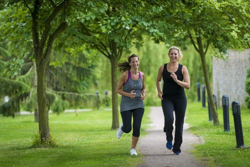 Two ladies running through Ragdale grounds